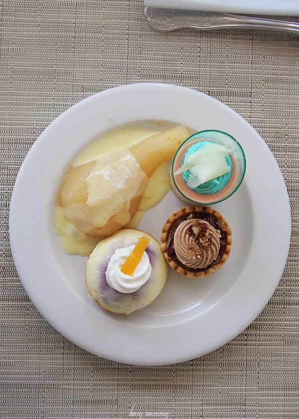 Desserts: Poached pears with white chocolate sauce, pecan tartlet and blueberry cheesecake.