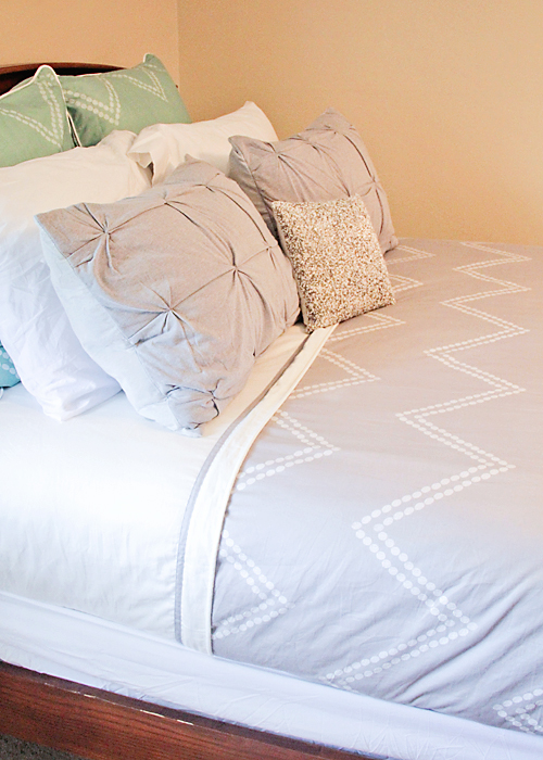 A beautifully made bed. I love the color scheme!