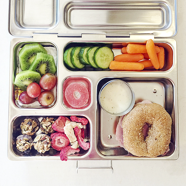 Lunchbox idea: ham on mini bagel, kiwi, grapes, cucumber, carrots, freeze dried fruit, energy bites and gummy.
